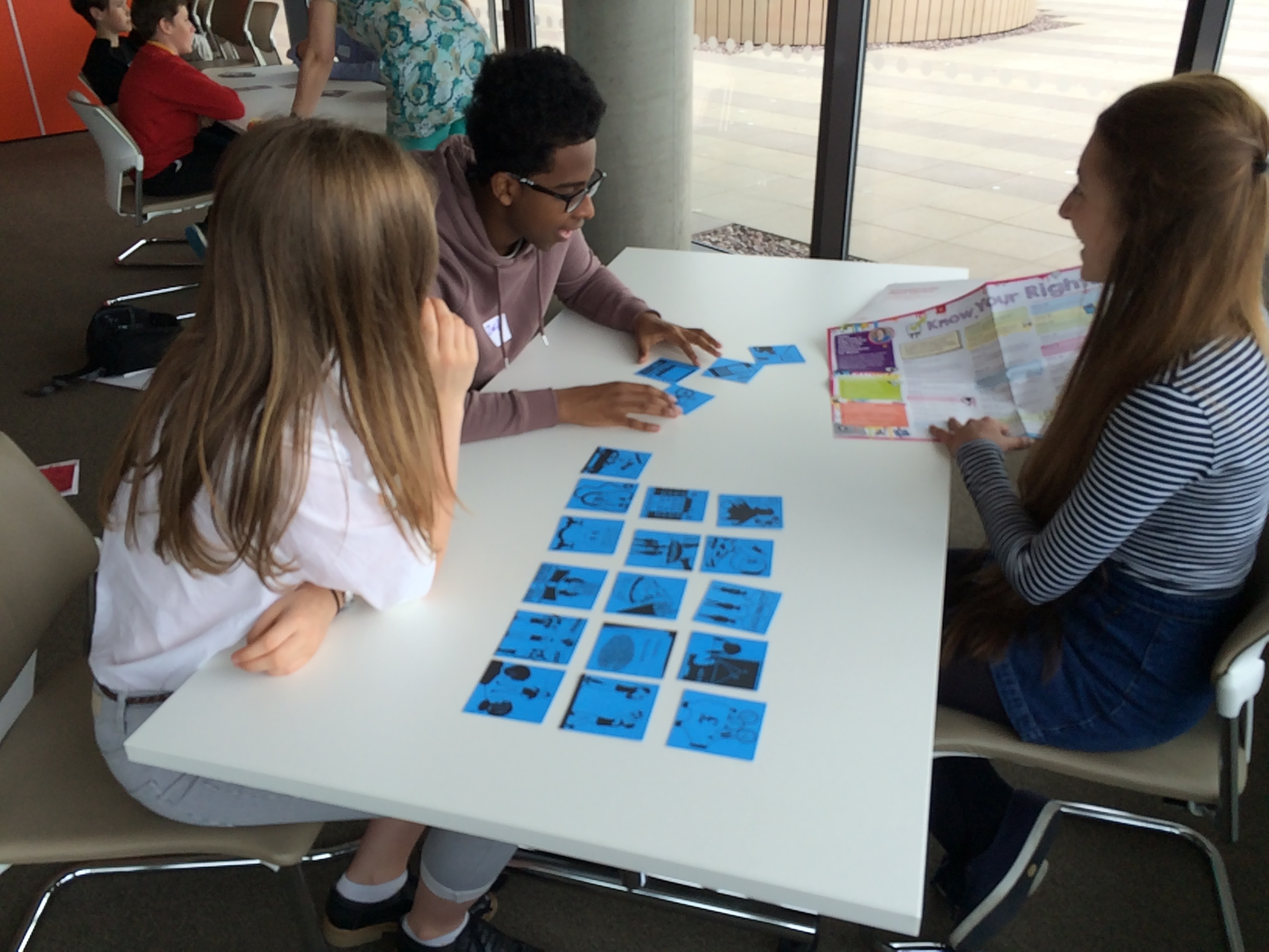 Three young people playing a want or need card game using the 'Know your rights' poster