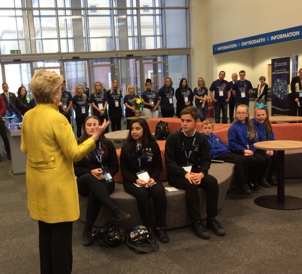 Hillary Clinton speaking to a room of children and young people.