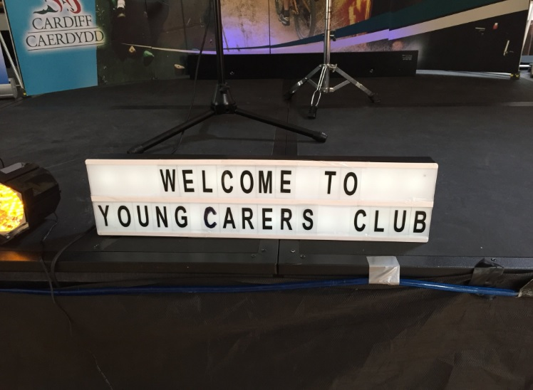 A sign saying 'WELCOME TO YOUNG CARERS CLUB' places on a stage.